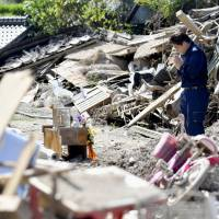 Nature's fury: A man in Asakura, Fukuoka Prefecture, prays for the victims of torrential rains that slammed Kyushu. The July storms triggered deadly floods and landslides across the north of the island. | KYODO