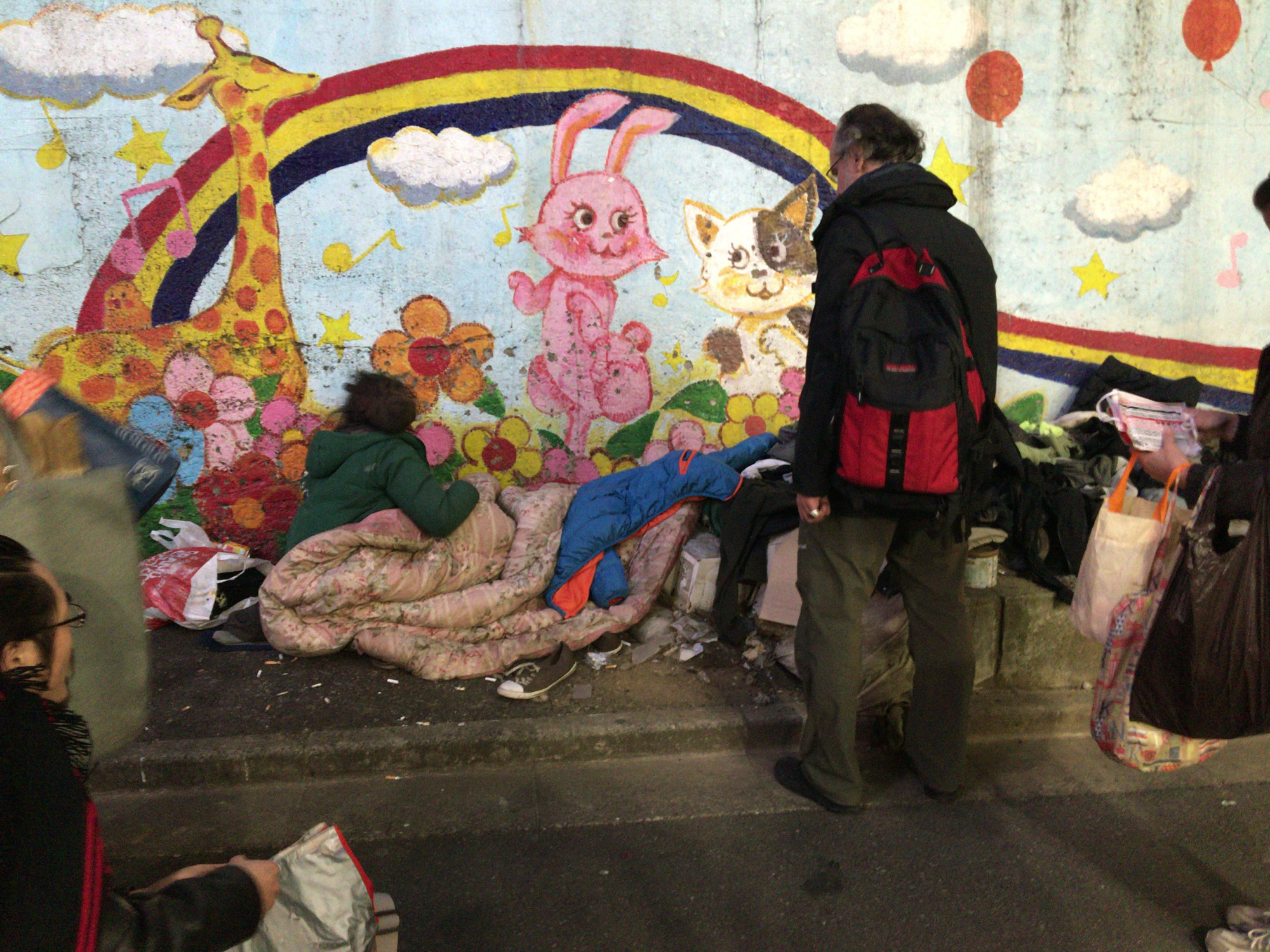 Study in contrasts: A homeless man sleeps next to a mural in Tokyo's Shinjuku district. | SIMON SCOTT