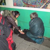 The gift of giving: Tokyo Spring Homeless Patrol volunteer Elena Quesada Diaz distributes candy and cookies to a homeless man near Shinjuku Station. | SIMON SCOTT