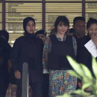 On trial: Vietnamese Doan Thi Huong is escorted by police as she leaves a court hearing in Shah Alam, outside Kuala Lumpur, in October.   AP