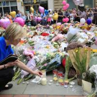 Candles of remembrance: A woman places a candle in front of a crowd that has gathered in Manchester, England, to honor the victims of a suicide bombing.   KYODO