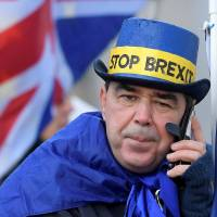 Hold the line: An anti-Brexit protestor speaks on his phone near the Houses of Parliament in London in December.   REUTERS