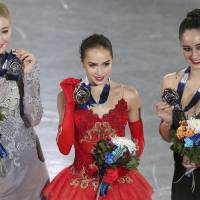 Russian gold medalist Alina Zagitova (center) is joined by compatriot and runner-up Maria Sotskova (left) and Canadian third-place finisher Kaetlyn Osmond for a group photo after receiving their awards on Saturday at the Grand Prix Final. | AP