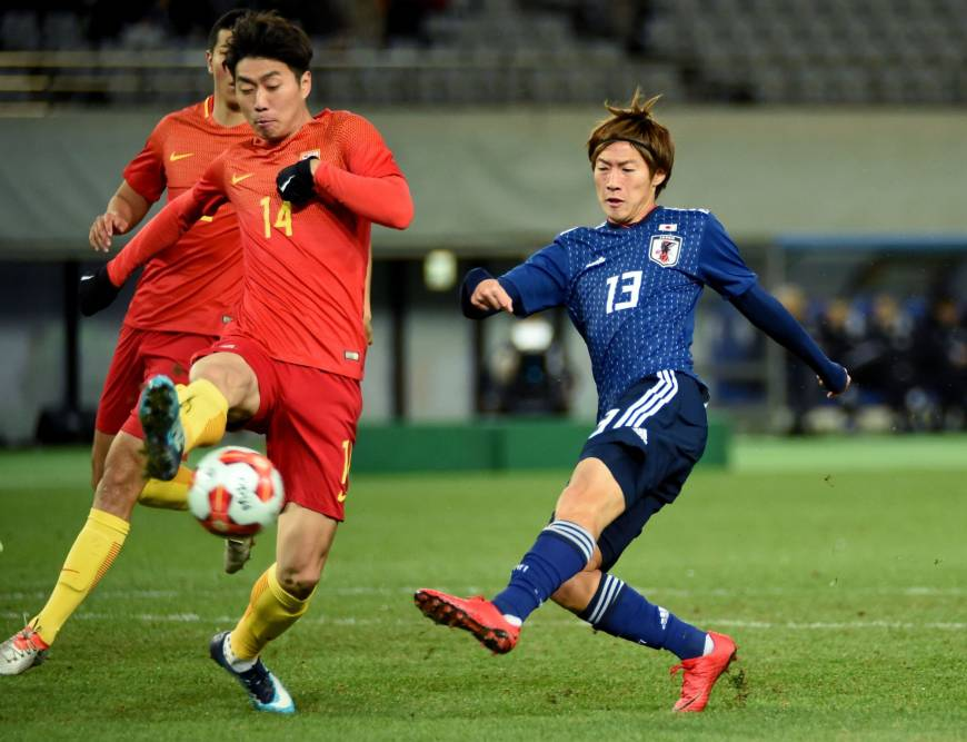 Shoma Doi (right) competes for the ball with China's Fu Huan during Japan's 2-1 win on Tuesday at the E-1 Football Championship at Tokyo's Ajinomoto Stadium. | AFP-JIJI