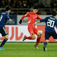 North Korea's Pak Song Chol controls the ball during Saturday's match against Japan. | AFP-JIJI