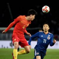 China's Gao Zhunyi (left) and Japan's Yu Kobayashi vie for the ball on Tuesday. | AFP-JIJI