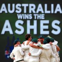The Australian team celebrates after beating England in the third Ashes test in Perth, Australia, on Monday to clinch the series. | REUTERS