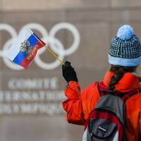 A woman waves a Russia flag outside the International Olympic Committee's headquarters in Lausanne, Switzerland, on Tuesday.   AP