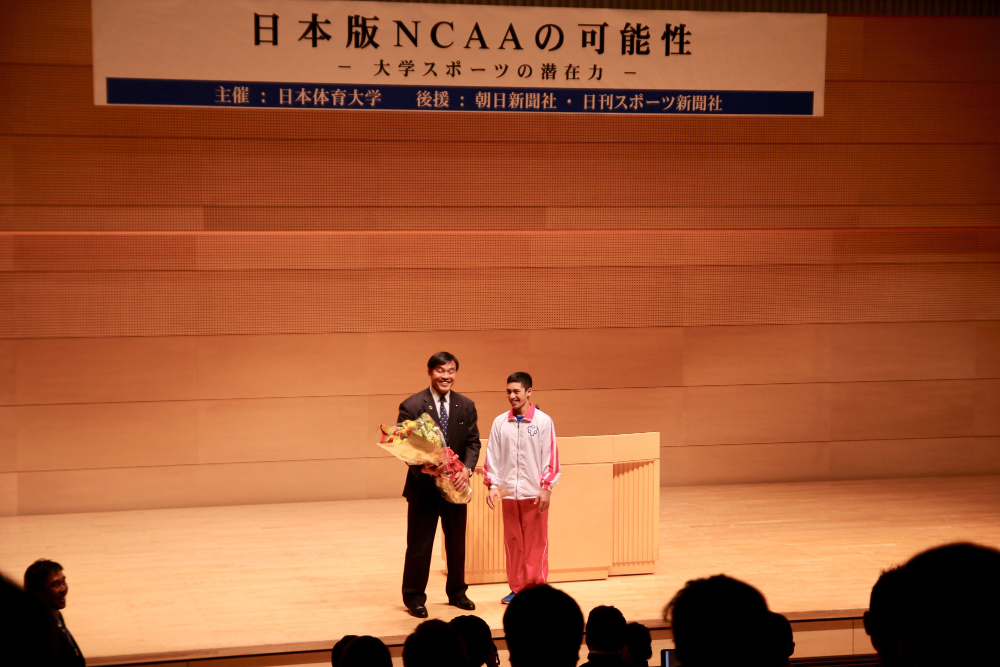 Former education minister and pro wrestler Hiroshi Hase (left) stands with gymnast Kenzo Shirai during a symposium on the creation of a Japanese version of the NCAA on Saturday at Nippon Sport Science University.   KAZ NAGATSUKA