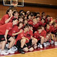 The players on the Japan women's national team and Under-24 and U-19 national teams pose for photos after wrapping up a two-day training camp  at Tokyo's National Training Center on Tuesday. | KAZ NAGATSUKA
