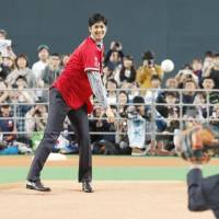 Shohei Ohtani throws a ball to Hokkaido Nippon Ham Fighters manager Hideki Kuriyama in front of fans at Sapporo Dome on Monday. | KYODO