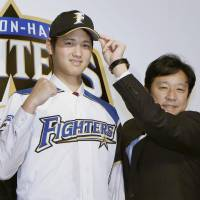 The Fighters' Shohei Ohtani and team manager Hideki Kuriyama pose for photos during a news conference to introduce the team's selections in the 2012 draft. After five seasons with Nippon Ham, Ohtani has decided to sign with the Angels in MLB for the 2018 season.   KYODO