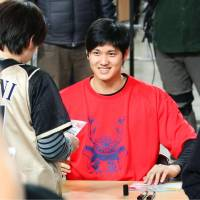 Shohei Otani is seen giving an autograph to a fan during a Hokkaido Nippon Ham Fighters' team event at Sapporo Dome on Nov. 26. | KYODO