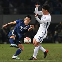 Japan defender Naomichi Ueda (left) tries to clear the ball away from South Korea's Kim Min-woo during the E-1 Football Championship in Tokyo on Dec. 16.   AFP-JIJI