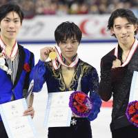 All-Japan Championship runner-up Keiji Tanaka (left), winner Shoma Uno (center) and third-place finisher Takahito Mura display their medals after Sunday's free skate. | KYODO