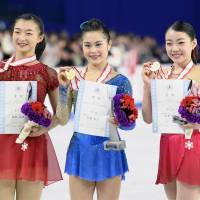 Winner Satoko Miyahara (center), runner-up Kaori Sakamoto (left) and third-place finisher Rika Kihira are seen after the women's free skate on Saturday night at the All-Japan Championships. | KYODO