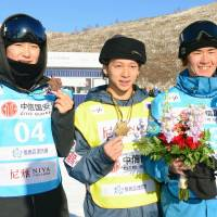 Winner Ayumu Hirano (center), runner-up Raibu Katayama (right) and third-place finisher Yuto Totsuka are seen after a snowboard World Cup  men's halfpipe event on Thursday in Zhangjiakou, China. | KYODO