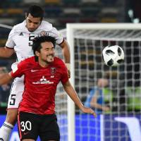 Urawa's Shinzo Koroki (right) and Al Jazira's Musallem Fayez vie for the ball during their Club World Cup quarterfinal match on Saturday in Abu Dhabi. | AFP-JIJI