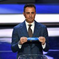 Former Italy defender Fabio Cannavaro displays the slip of Japan during the 2018 FIFA World Cup Draw in Moscow on Friday night. Japan was drawn into Group H along with Colombia, Senegal and Poland. | AFP-JIJI