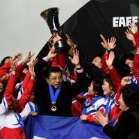 North Korea women's head coach Kim Kwang Min holds the winner's trophy and celebrates with his players after their 2-0 victory over Japan in the E-1 Football Championship final at Fukuda Denshi Arena. | AFP-JIJI