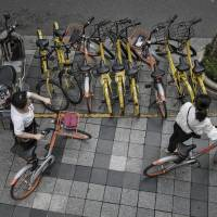 Cyclists try to park Mobike bicycles on a crowded street in Shanghai. | BLOOMBERG