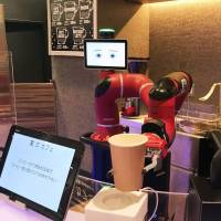 A robotic arm holds a paper cup at a cafe in Tokyo's Shibuya Ward on Tuesday. | KYODO