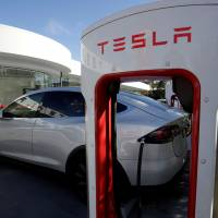 A Tesla Model X vehicle is charged by a supercharger outside a Tesla electric car dealership in Sydney. | REUTERS