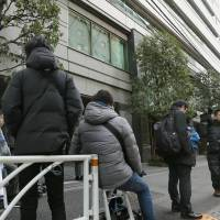 Journalists wait outside the building from which embattled cryptocurrency trader Coincheck operates, in Shibuya Ward, Tokyo, on Monday. | KYODO