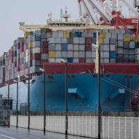 A container ship sits berthed at a shipping terminal in Yokohama, Japan. Japan's current account surplus in November marked the 41st straight month of black ink, with increased shipments of semiconductor-related equipment and cars lifting the country's exports by 13.9 percent to ¥6.77 trillion. | BLOOMBERG