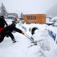Staff remove snow ahead of the World Economic Forum (WEF) annual meeting in the Swiss Alps resort of Davos Sunday. | REUTERS