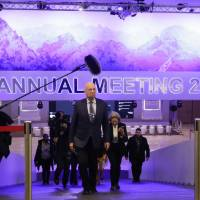 Followed by a television team and assistants, Klaus Schwab, founder and executive chairman of the World Economic Forum, walks through the meeting's conference center in Davos, Switzerland, Sunday. The meeting brings together entrepreneurs, scientists, chief executives and political leaders from Tuesday to Jan. 26. | AP