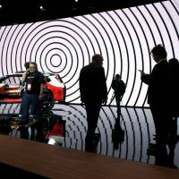 People look at a Nissan Xmotion SUV concept car onstage at their booth at the North American International Auto Show in Detroit Monday. | REUTERS