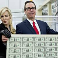 Steven Mnuchin, U.S. Treasury secretary, right, and his wife Louise Linton hold an uncut sheet of one-dollar notes at the U.S. Bureau of Engraving and Printing in Washington, D.C., U.S., on Wednesday, Nov. 15, 2017. | BLOOMBERG