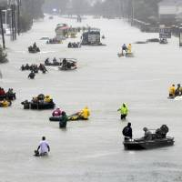 Rescue boats float on a flooded street as people are evacuated from rising floodwaters brought on by Tropical Storm Harvey in Houston last August. The National Hurricane Center's official report on Harvey compiles staggering numbers, starting with 68 dead and $125 billion in damage. But the really big numbers in the Thursday tally have to do with the rainfall that swamped Houston. Two places had more than 5 feet of rain. | AP