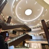 Members of the media on Tuesday tour the first-floor atrium of Tokyo Midtown Hibiya, a new commercial and office complex in Chiyoda Ward scheduled to open in March. | YOSHIAKI MIURA