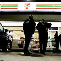 U.S. Immigration and Customs Enforcement agents serve an employment audit notice at a 7-Eleven convenience store Wednesday in Los Angeles. Agents said they targeted about 100 7-Eleven stores nationwide Wednesday to open employment audits and interview workers. | AP