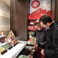 Foreign visitors look at Nestle Japan's wasabi KitKat bars at the company's outlet in Tokyo's Ginza shopping district in late November. | YOSHIAKI MIURA