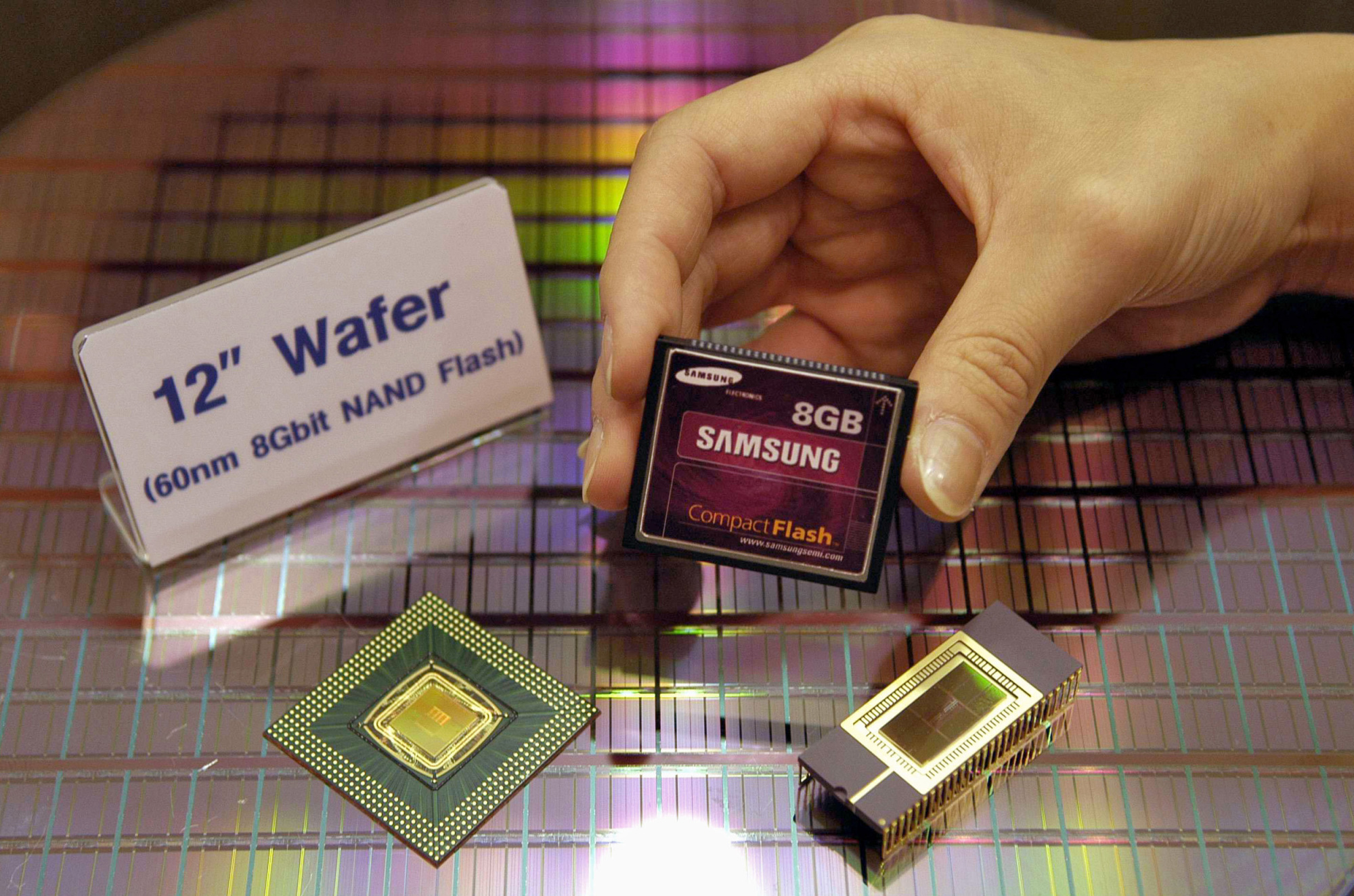 A compact NAND flash memory card and other Samsung Electronics Co. Ltd. products are shown during a 2004 conference. Some analysts expect the memory chip industry's growth rate to fall by more than half this year. | BLOOMBERG