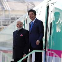 Prime Minister Shinzo Abe and Indian Prime Minister Narendra Modi leave an E5 series shinkansen during a visit to a plant run by Kawasaki Heavy Industries Ltd.'s Rolling Stock Co. in Kobe in 2016. | BLOOMBERG