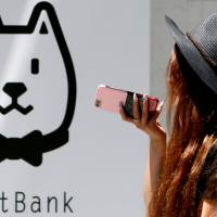 A woman holding a smartphone passes a SoftBank outlet in Tokyo. The conglomerate is planning to list its telecom unit on the Tokyo Stock Exchange by the end of the year.   REUTERS