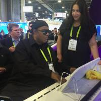Musician Stevie Wonder plays a 'smart' piano, an internet-connected device designed to teach people how to play, while piano teacher Gabie Perry stands next to him at The One Music Group's CES booth in Las Vegas Wednesday. Wonder spent about 15 minutes playing tunes as a crowd gathered at the booth. Wonder says he likes to visit the conference to see new things and meet people. | AP