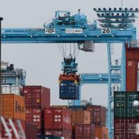 A gantry crane moves a container at a shipping terminal in Yokohama. Japan's exports rose almost 12 percent in 2017.   BLOOMBERG