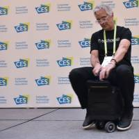 An exhibitor demonstrates the MODOBAG at the Venetian during CES 2018 in Las Vegas on Tuesday. The bag is a carry-on suitcase that converts into a scooter. | AFP-JIJI
