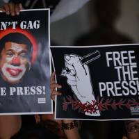 Journalists and supporters display placards depicting Philippine President Rodrigo Duterte as a clown during a protest backing press freedoms in Manila on Friday. | AFP-JIJI