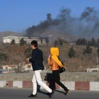 Afghans run near the Intercontinental Hotel as smoke billows during a fight between gunmen and Afghan security forces in Kabul on Sunday. | AFP-JIJI