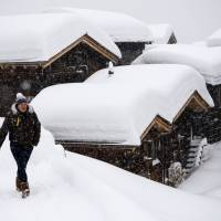 A person walks in front of chalets covered with fresh snow, in Bellwald, Switzerland, on Sunday. Heavy snowfall increased the risk of avalanches in almost all the Swiss mountains. | JEAN-CHRISTOPHE BOTT / KEYSTONE / VIA AP