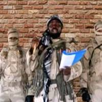 The leader of one of the Boko Haram group's factions, Abubakar Shekau, speaks in front of guards in an unknown location in Nigeria in this still image taken from an undated video obtained on Monday. | BOKO HARAM HANDOUT / SAHARA REPORTERS / VIA REUTERS