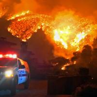 A fire burns canyons and ridges above Bella Vista Drive, near Romero Canyon, in Montecito, California, on Dec. 12. The largest wildfire on record in California, the Thomas fire, was declared contained Friday, days after mud on the coastal mountain slopes it scorched crashed down on homes during a storm, killing at least 18 people. | AP
