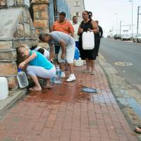 People collect drinking water from pipes fed by an underground spring in St. James, about 25 km from Cape Town's center on Jan 19. Cape Town will next month slash its individual daily water consumption limit by 40 percent to 50 liters, the mayor said on Jan. 18, as the city battles its worst drought in a century. | AFP-JIJI