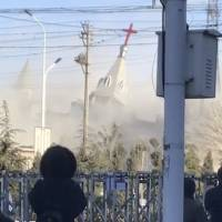 People watch the demolition of the Golden Lampstand Church in Linfen, in northern China's Shanxi province, on Tuesday in this image taken from video. | CHINA AID / VIA AP